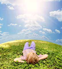 Lying on green grass carefree boy