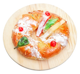 Portuguese king cake on a wooden stand. On a white background. I