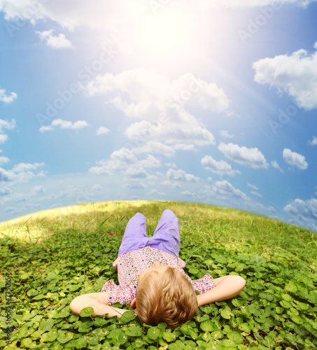 Lying on green grass carefree boy