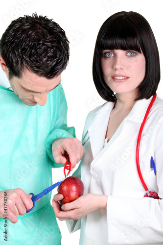 Surgeon operating on apple