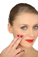 Woman with red nail varnish and lipstick