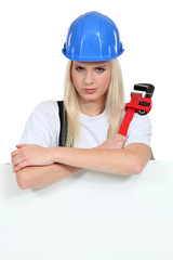 Woman with a wrench and board left blank for your message
