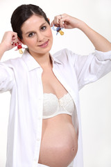 Pregnant woman holding pacifiers