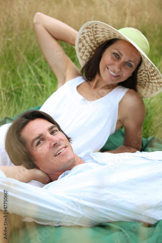 40 years old man and woman relaxing and  lying down in a meadow