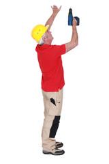 senior craftsman holding a drill