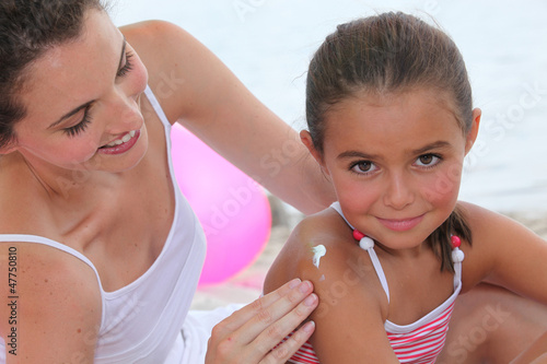 Mother putting suncream on her daughter.