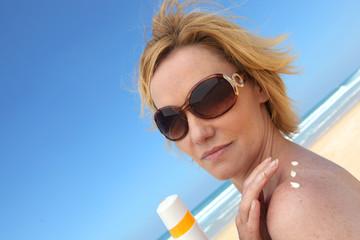 Woman at beach applying sun cream