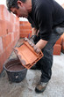 Mason spreading cement on brick