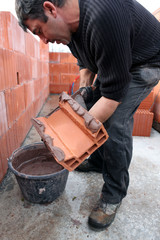 Mason spreading cement on brick