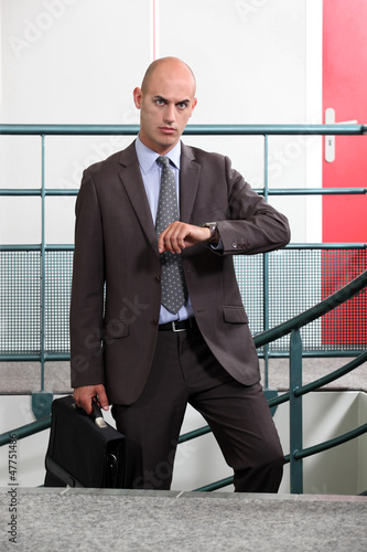 An angry businessman looking at the time
