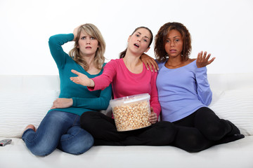 friends watching television and eating popcorn