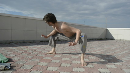Man practices yoga on the roof. Squats.