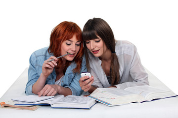 Young women taking a break from studying to read a text message