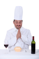 chef sitting between glass of wine and facing hamburger