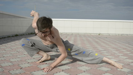 Man practices yoga on the roof. Squat on one leg.