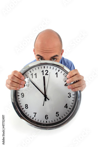 Covering his face with clock