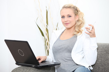 Young woman sitting on the couch with a laptop and cup of tea
