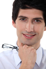 Close-up portrait of a smiling man holding his glasses