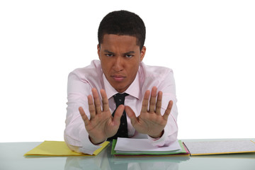 Man at desk making stop gesture