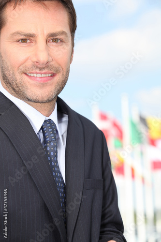 Businessman standing in front of international flags