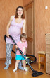 mother and daughter chores with vacuum cleaner