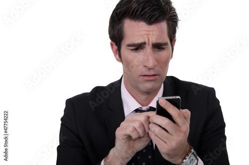 An anxious man texting.