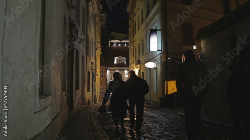 Old city at night. Silhouettes of people.