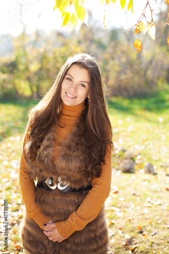 Cute young woman with luxurious hair posing in the park.