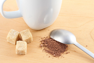 Cacao powder and sugar next to a cup and a spoon