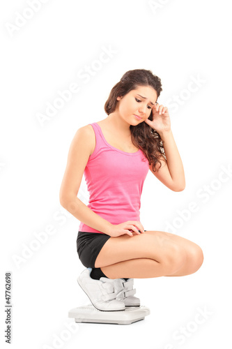 A disappointed young female standing on a weigh scale