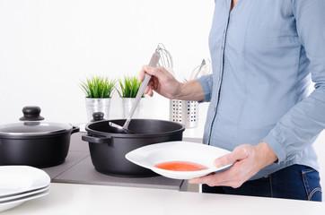 Frau füllt Suppe in einen Teller