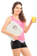 A smiling female athlete holding a weigh scale and glass of ora