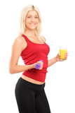 Attractive female athlete holding a dumbbell and glass of juice