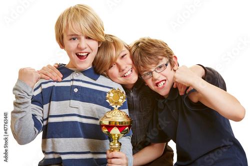 Drei Jungs mit Pokal jubeln