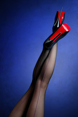 Slim female legs in dark stockings wearing high heels over