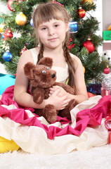 Beautiful little girl in holiday dress with toy in hands in
