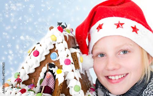 Mädchen mit Weihnachtsmütze und Pfefferkuchenhaus
