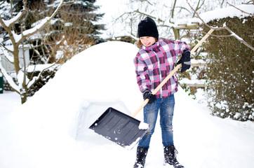 Mädchen mit Schneeschieber vor dem Iglu