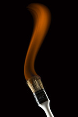 Burning paintbrush on black background painting with fire