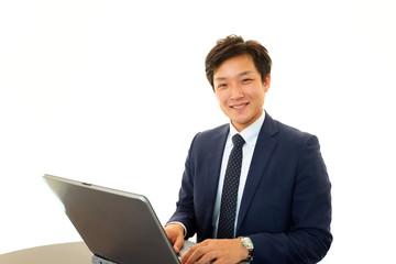 パソコンで仕事中の笑顔のビジネスマン