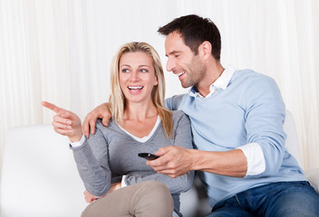Cheerful couple watching TV