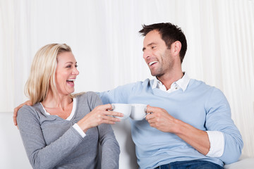 Happy couple enjoying a cup of tea or coffee