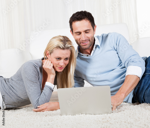 Couple lying on a carpet with a laptop
