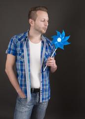 Verträumter junger Mann in Blau mit Windrad