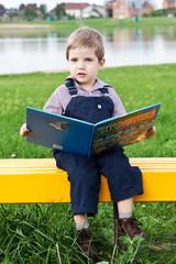 Милый мальчик в парке читает книгу