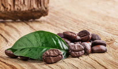 Coffee grains and green leaf on wooden table