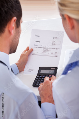 Colleagues checking an invoice on a calculator