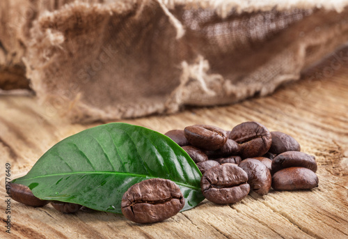 Coffee grains and green leaf on old wooden board