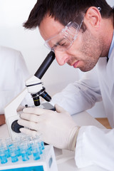 Pathologist or lab technician using a microscope