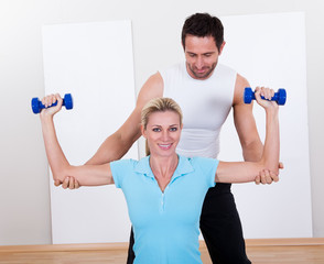 Fitness instructor helping a woman workout